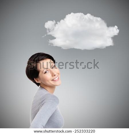 Smiley joyful woman with cloud, isolated on grey - stock photo