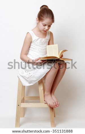 Smiley little girl holding vintage books - stock photo