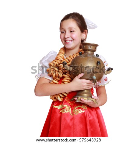 Smiley little girl wearing russian  traditional costume and holding round cracknel and vintage samovar isolated over white background