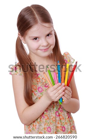 smiley little girl with colorful pencils/European first grader holding pencils on white background - stock photo