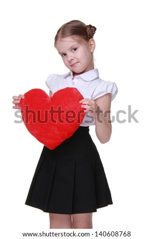 Smiley little schoolgirl with nice hairstyle posing with heart shape on Holiday theme/Charming schoolgirl wearing white blouse and black skirt and holding red love symbol