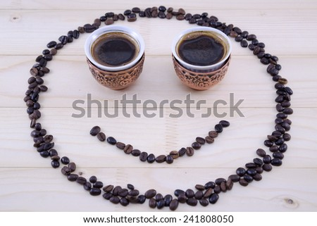 Smiley made out of coffee grains and two vintage cups of coffee as eyes - stock photo