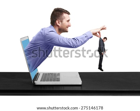 smiley man got out of the computer and keeping the small sad man over white background - stock photo
