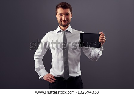 smiley man in formal wear holding tablet pc and looking at camera
