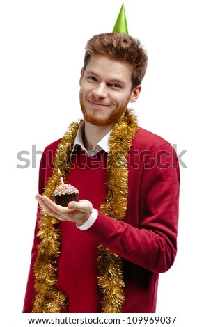 Smiley man with tinsel and fool's cap holds small cake, isolated on white