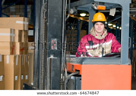 smiley man worker sitting in industrial stacker at warehouse - stock photo