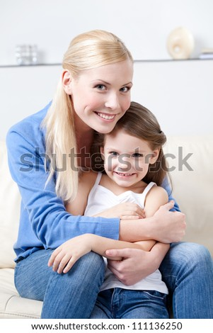 Smiley mother hugs her daughter on the sofa - stock photo