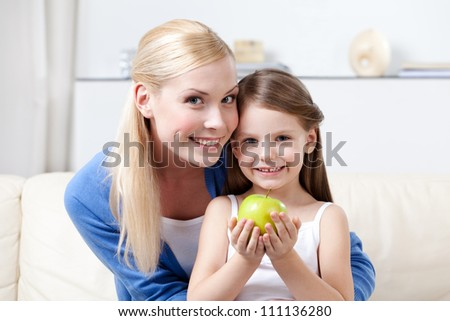 Smiley mummy with her keeping sweet green apple daughter - stock photo