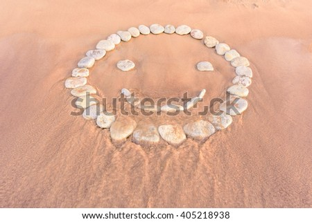 Smiley of pebbles on the sandy beach - stock photo