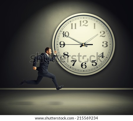 smiley running businessman and big white clock in dark room - stock photo