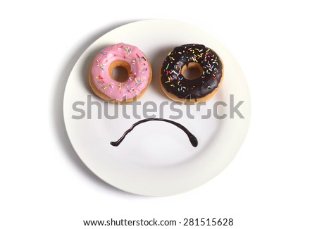smiley sad face worried about overweight made on dish with donuts as eyes and chocolate syrup as mouth in sugar and sweet addiction , diet and nutrition concept isolated on white background  - stock photo