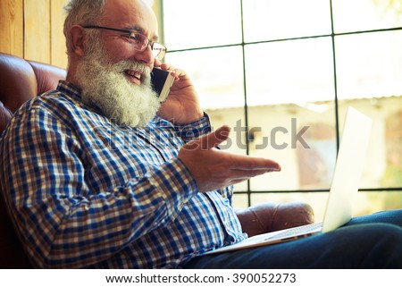 smiley senior man sitting on the couch with laptop and talking on the phone at home