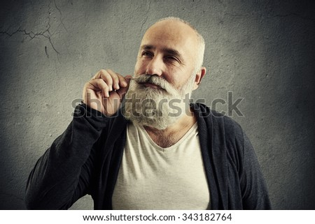 smiley senior man twisting his mustache and dreaming looking up over grey background - stock photo