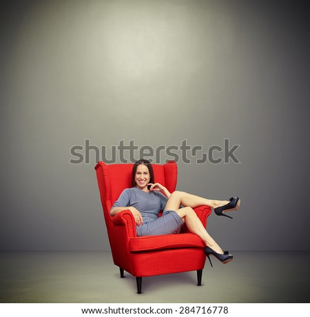 smiley sexy woman relaxing on red chair with empty copyspace overhead in grey room