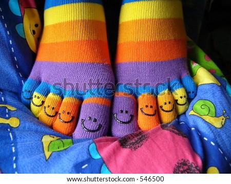 Smiley socks on smiley coverlet - stock photo