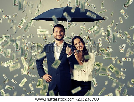 smiley successful couple with umbrella standing under money rain - stock photo