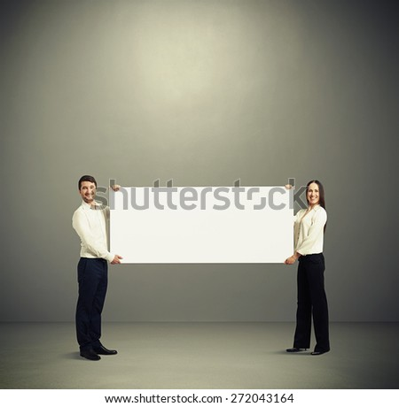 smiley woman and man holding white banner and looking at camera over grey background with empty copyspace - stock photo