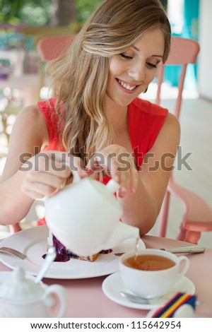 smiley woman pouring the cup of tea and smiling. shot in the cafe - stock photo