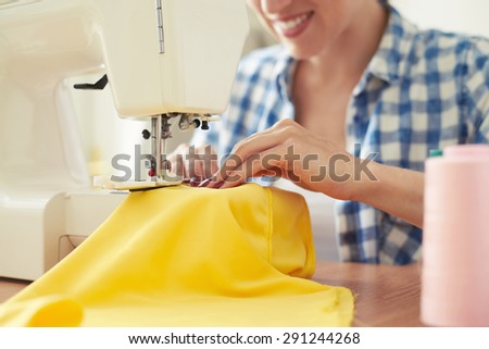 smiley woman sewing on sewing-machine. focus on sewing-machine - stock photo