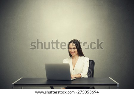 smiley woman sitting at the table with laptop, typing on keyboard and looking at screen over dark grey background with empty copyspace overhead - stock photo
