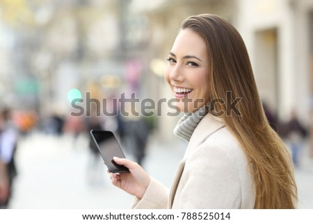Smiley woman using a mobile phone and looking at camera on the street in winter