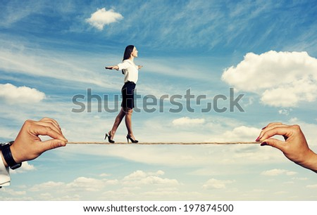 smiley woman walking on the rope over blue sky - stock photo