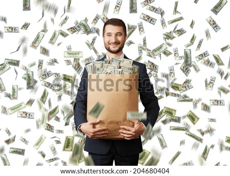 smiley young businessman holding paper bag with money under dollar's rain - stock photo
