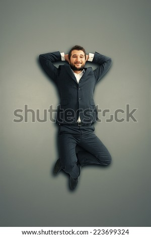 smiley young businessman lying on the grey floor and looking at camera - stock photo