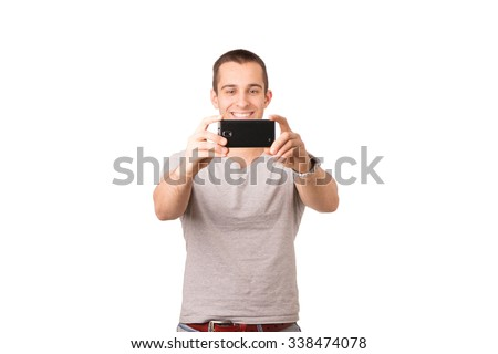Smiley young man taking selfie - stock photo