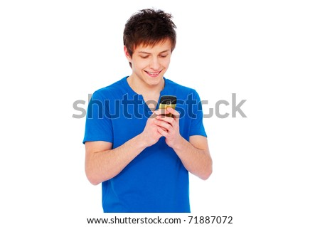 smiley young man text messaging on mobile phone against white background - stock photo