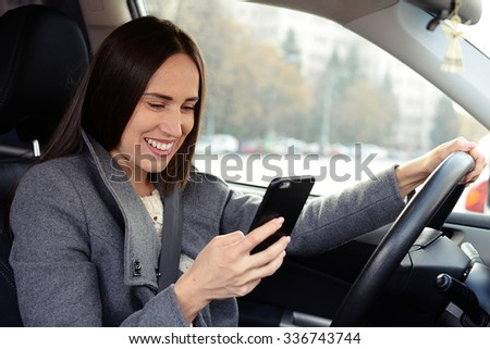 smiley young woman driving the car and chatting on smartphone