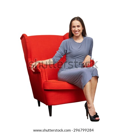 smiley young woman in dress sitting on red chair and looking at camera. isolated on white background - stock photo