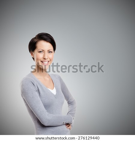 Smiley young woman, isolated on grey - stock photo