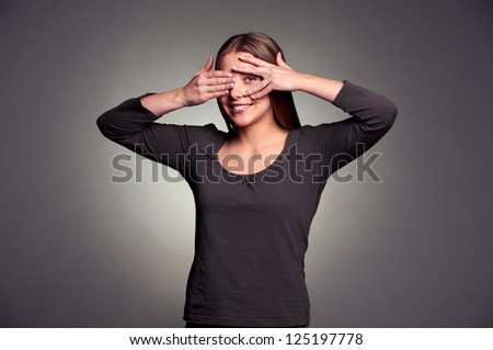 smiley young woman peeping through her fingers. studio shot over dark background - stock photo
