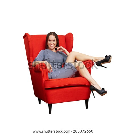 smiley young woman sitting on red chair and looking at camera. isolated on white background - stock photo