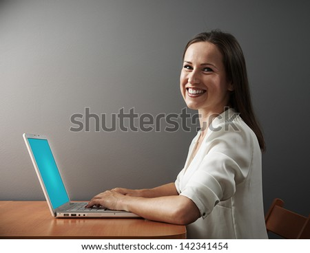 smiley young woman working with laptop and looking at camera