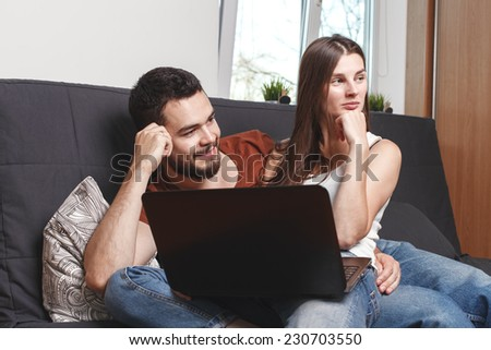 smilied couple with a laptop sitting on sofa at their home