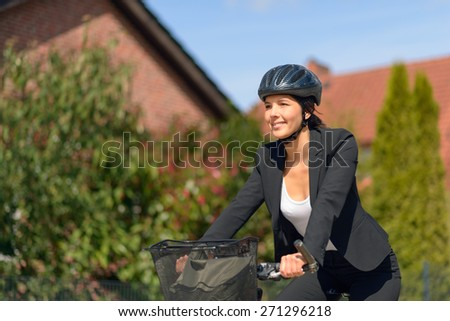 Smiling Active Young Businesswoman Riding a Bicycle with Helmet Going to her Office. - stock photo