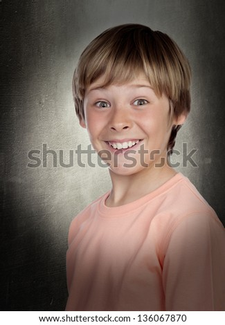 Smiling adolescent with a happy gesture on gray background - stock photo
