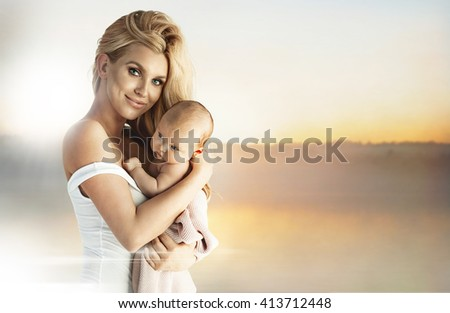 Smiling adorable blond mom with newborn baby - stock photo