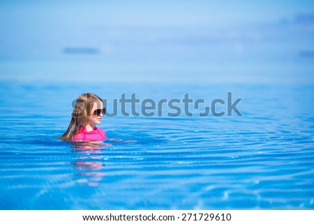 Smiling adorable girl having fun in outdoor swimming pool - stock photo