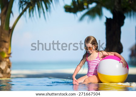 Smiling adorable girl playing with inflatable toy ball in outdoor swimming pool - stock photo
