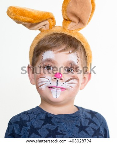 smiling adorable kid with paintings on his face and ears on - stock photo