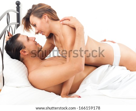 Smiling adult couple having sex on bed in bedroom interior at home