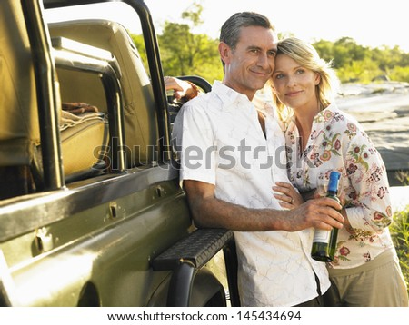 Smiling adult couple standing by jeep with a bottle of wine - stock photo
