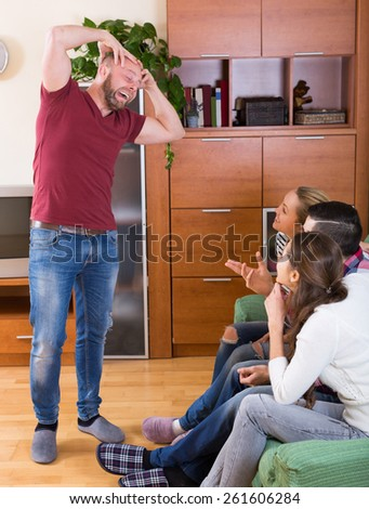 smiling adult friends hanging out with beer and jokes at home   - stock photo