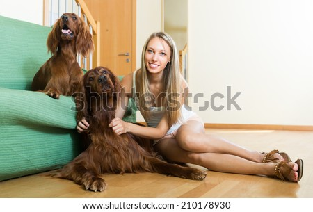 Smiling adult girl playing with two Irish setters on the floor at home. Focus on dog