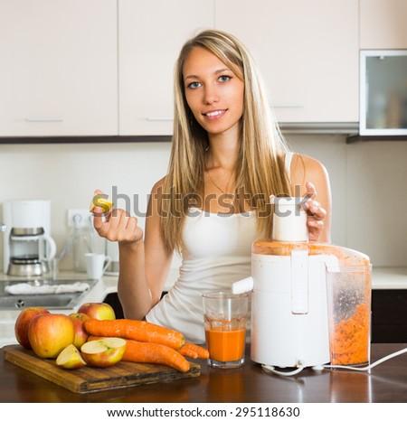 Smiling adult girl preparing fresh juice in domestic kitchen - stock photo