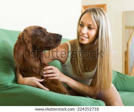Smiling adult girl sitting on sofa at home and hugging red Irish setter  - stock photo