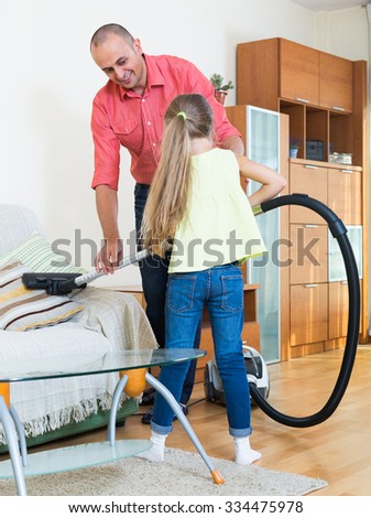 Smiling adult man teaching little girl vacuuming during clean-up